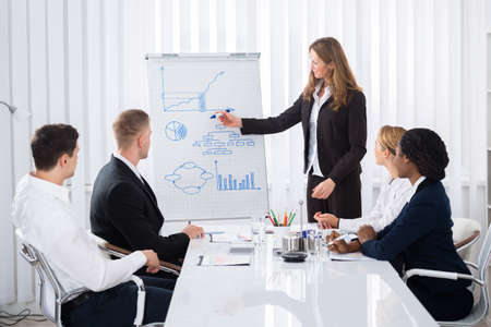 Group Of Businesspeople Looking At Confident Businesswoman Explaining In Presentation