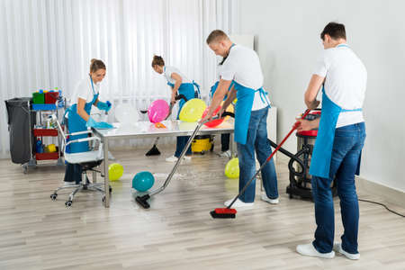 after the party: Group Of Male And Female Janitors Cleaning The Office After Party