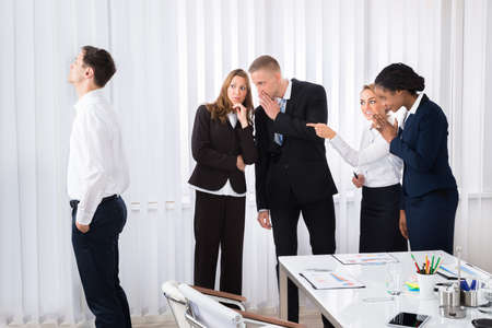 gossiping: Businesspeople Gossiping Behind Young Colleague In Office