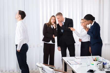 acoso laboral: Los empresarios del cotilleo colega detrás de joven en oficina