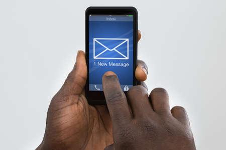 letras negras: Primer Del Teléfono Móvil persona que sostiene que muestra un nuevo mensaje en la pantalla Un Foto de archivo