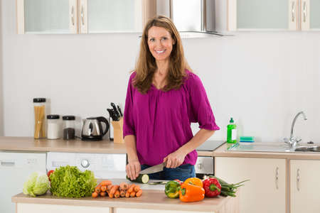 woman eating: Smiling Woman Cutting Vegetable On Chopping Board In Kitchen