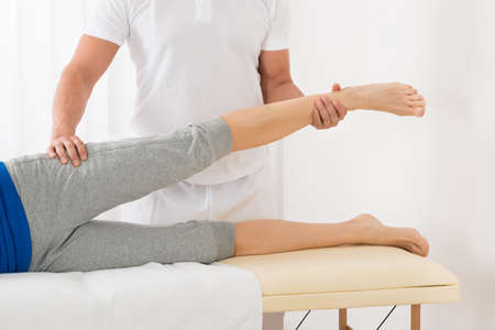 pressure massage: Close-up Of Male Therapist Giving Leg Massage To Woman Stock Photo