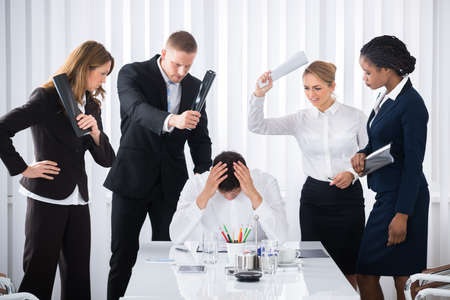 blaming: Group Of Angry Businesspeople Blaming Male Colleague In Meeting Stock Photo