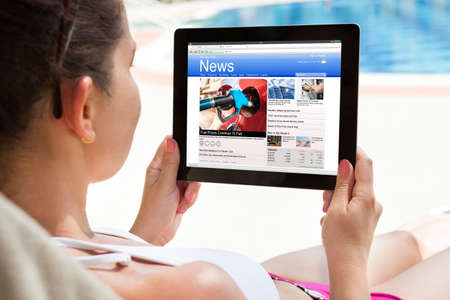 articles: Close-up Of Woman Reading News On Digital Tablet