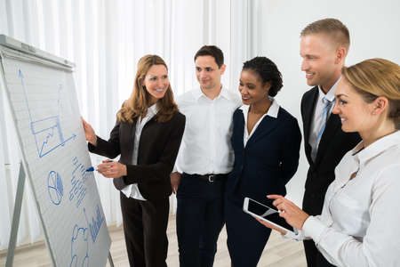 Happy Female Manager Explaining Business Strategy To The Staffs In Office