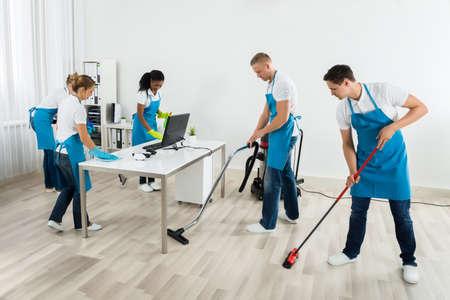 Gruppe der männlichen und weiblichen Janitors In Uniform The Office Reinigungs Lizenzfreie Bilder