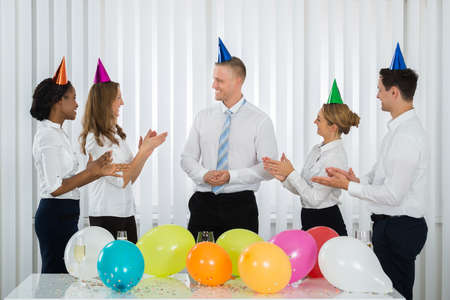 applauding: Group Of Businesspeople Applauding To The Manager During Party In Office