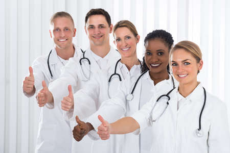 medical practitioner: Team Of Happy Medical Practitioner Standing In A Line Stock Photo