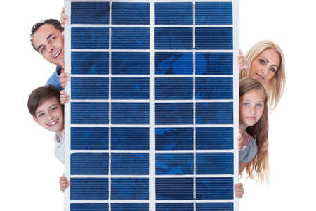 Portrait Of A Happy Family Peeping From Solar Panel Against White Background photo
