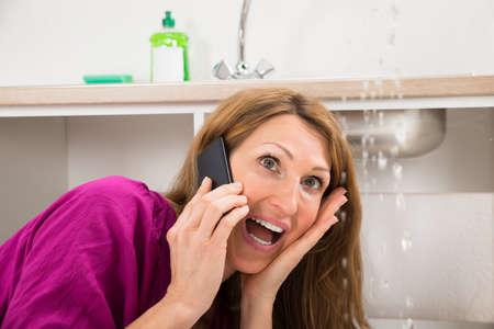 Close-up der Frau unter den Klempner anrufen, während Wasser aus Sink Undichte Standard-Bild - 57754091