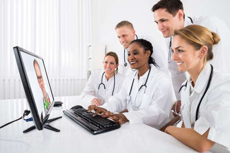 videoconferencing: Group Of Doctors Videoconferencing On Computer In Hospital Stock Photo