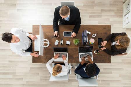 Los empresarios profesionales usando los ordenadores y portátiles en la oficina