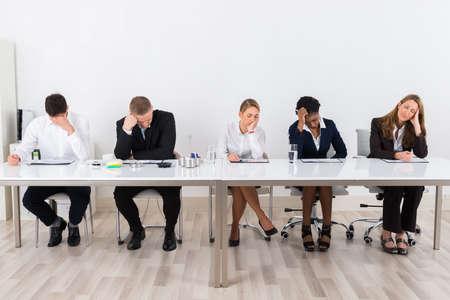 Groep Van Geprobeerd Ondernemers zitten in een rij Op Kantoor Stockfoto