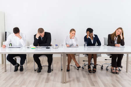 boardroom: Group Of Tried Businesspeople Sitting In A Row At Office