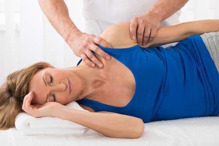 physical therapist: Close-up Of Person Giving Massage To Mature Woman In Spa