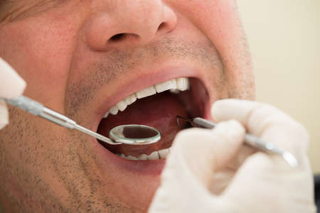 examined: Mature Man Examined By Dentist In Clinic