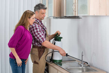 Woman Looking At Male Worker Spraying Insecticide In Kitchen