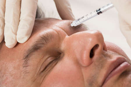 Receiving: Mature Man Receiving Cosmetic Injection With Syringe In Clinic