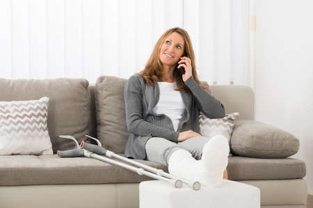 broken leg: Mature Woman With Plastered Leg Talking On Mobile Phone At Home