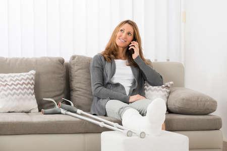 pierna rota: Mujer madura con la pierna enyesada habla en el teléfono móvil en el hogar