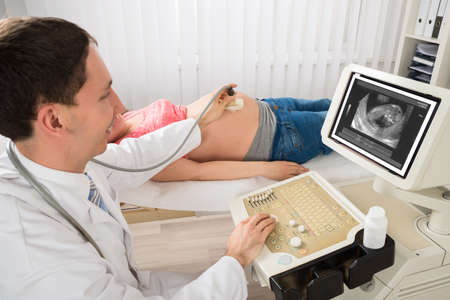 transducer: Happy Male Doctor Moving Ultrasound Transducer On Pregnant Womans Belly While Looking At Screen