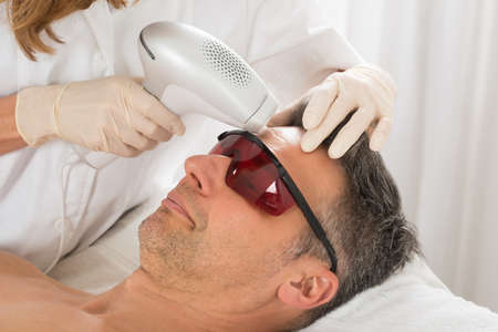 Mature Man Receiving Laser Epilation Treatment At Beauty Clinic