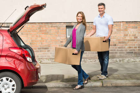 putting in: Mature Happy Couple Carrying Box For Putting In Car