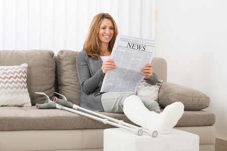 broken leg: Mature Woman With Fractured Leg Reading Newspaper In House Stock Photo
