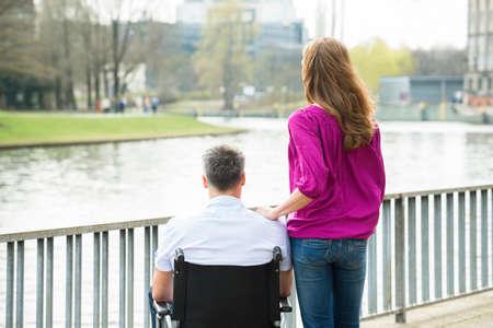 Vue arrière de la femme avec son mari handicapé sur fauteuil roulant Regardant le lac