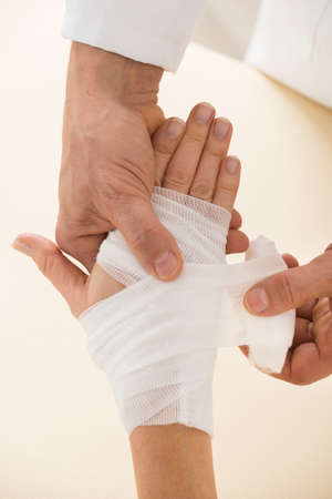 sprained joint: Close-up Of Person Hand Wrapping Bandage To Patient