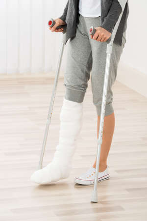 plaster leg cast: Close-up Of Woman Leg In Plaster Cast Using Crutches While Walking