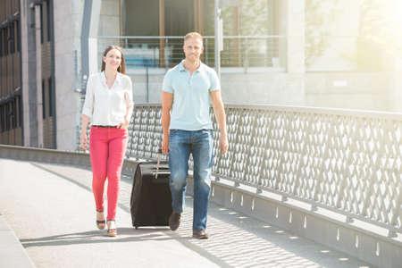 valise voyage: Portrait de jeune heureux couple marchant sur le pont avec des bagages