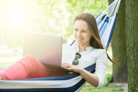 Smiling Woman Using Laptop While Lying In Hammock
