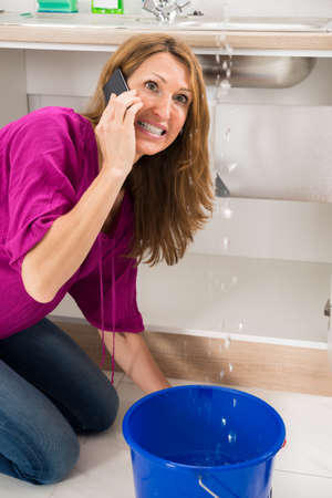 leakage: Angry Woman Calling To Plumber While Leakage Water Falling Into Bucket