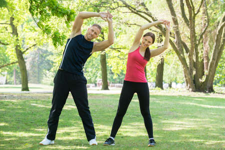couple exercising: Photo Of Young Couple Exercising Together In Park