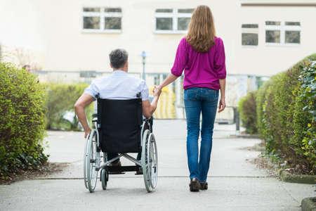 Vista trasera de la mujer con su marido para discapacitados en silla de ruedas en la calle Foto de archivo