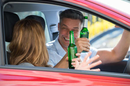 buy car: Close-up Of Happy Mature Couple Sitting Inside The Car Enjoying Beer