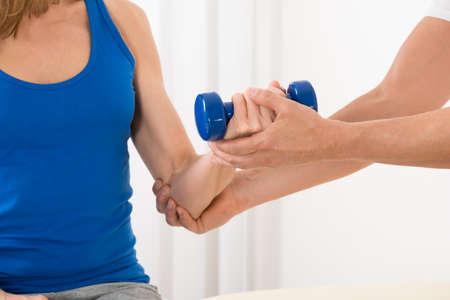 Primer plano, instructor, ayudando, mujer, ejercicio, azul, Dumbbell