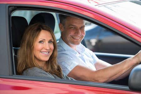 uomo rosso: Coppie mature felici seduto in auto nuova