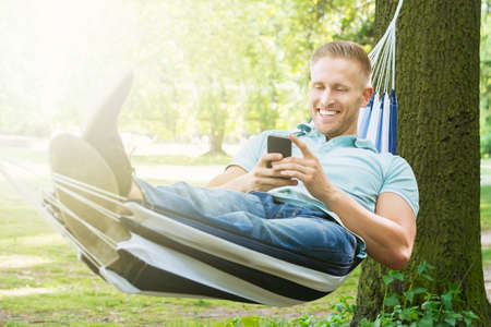 people relax: Young Happy Man Using Mobile Phone While Relaxing In Hammock At Garden