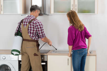 insecticide: Woman Looking At Male Worker Spraying Insecticide In Kitchen