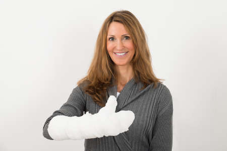 sprained joint: Portrait Of Happy Mature Woman With Broken Hand In Bandage