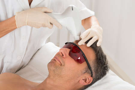 Mature Man Receiving Laser Epilation Treatment At Beauty Clinic