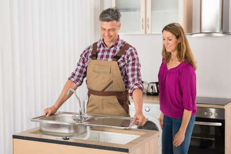 stainless steel sink: Woman Looking At Male Plumber Fixing Stainless Steel Sink Stock Photo