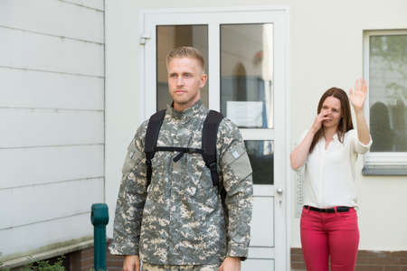 military men: Unhappy Young Wife Waving Goodbye To Male Soldier Outside House Stock Photo