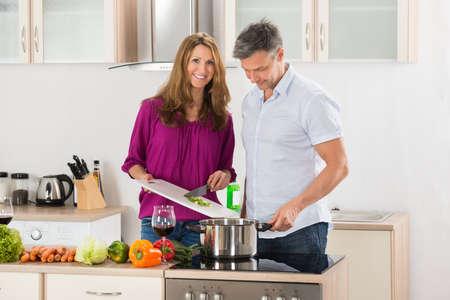 marido y mujer: Mujer preparación de alimentos, mientras que su marido sosteniendo el vaso de vino en cocina Foto de archivo