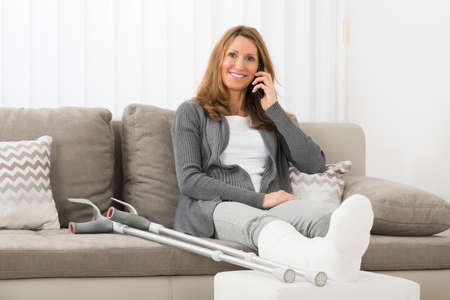 crutch: Mature Woman With Plastered Leg Talking On Mobile Phone At Home