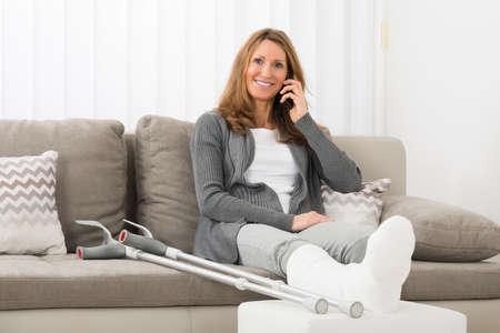 Mulher madura com perna rebocada, falando no celular em casa Foto de archivo