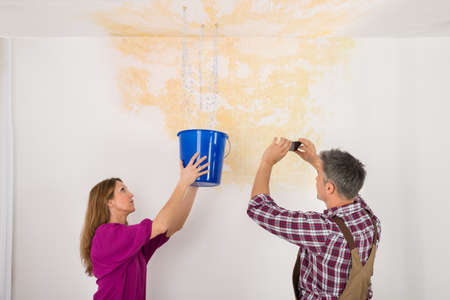 drop ceiling: Male Worker Photographing Water Damaged Ceiling While Woman Collecting Water In Bucket Stock Photo